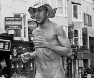 Hens with Pens life model Lorenzo running along a street nude, wearing only a straw hat